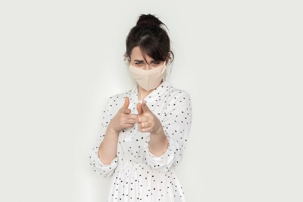 Nette brünette frau mit medizinischer maske gestikuliert einen schuss auf kamera