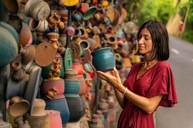 Nette brünette weibliche person, die in halber position auf dem markt steht und geschenke für ihre freunde auswählt
