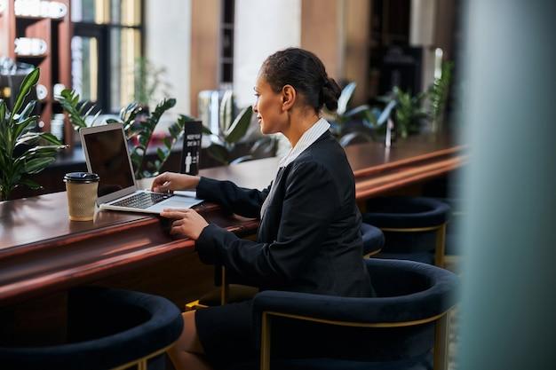 Nette brünette weibliche person, die in halber position sitzt und beim lesen von nachrichten auf den bildschirm des laptops schaut