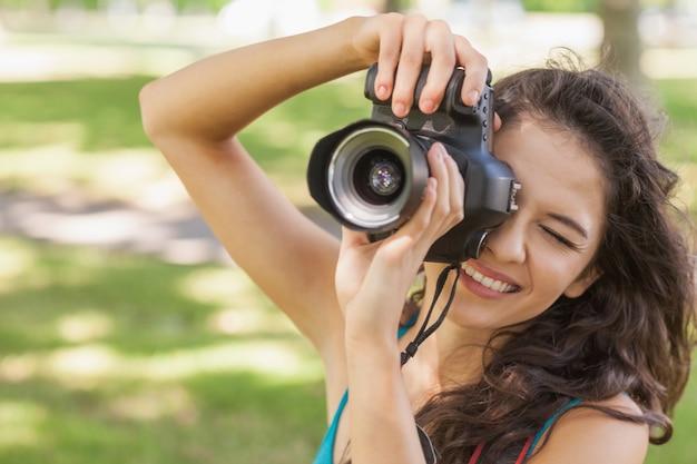 Nette brunettefrau, die ein foto mit ihrer kamera macht