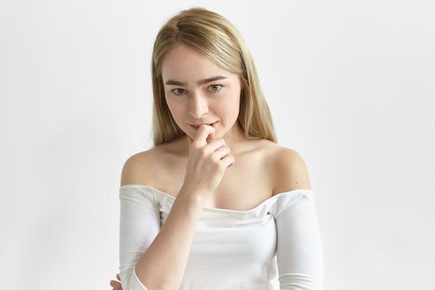 Nette charmante junge europäische frau in nackten schultern oben flirtet mit ihnen, schaut mit spielerischem lächeln, berührt ihre lippen.