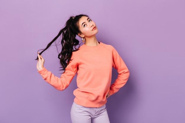 Nette chinesische junge frau, die mit haaren spielt. studioaufnahme der entzückenden asiatischen frau, die mit hand auf hüfte lokalisiert auf lila hintergrund steht.