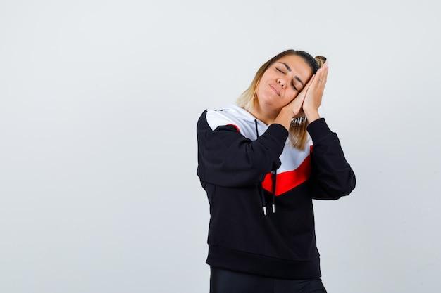 Nette dame, die sich auf palmen als kissen im hoodie stützt und schläfrig aussieht. vorderansicht.