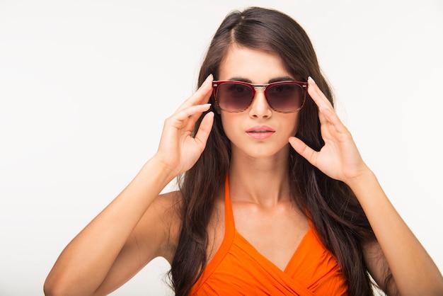 Nette dame im orangefarbenen hemd schaut tief.