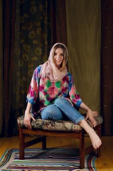 Nette dame im seidenschal um ihren kopf, der auf sofa mit buntem stoff aufwirft