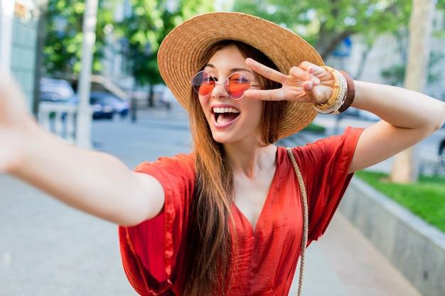 Nette dame im stilvollen hut, der selfie beim gehen im freien an sommerwochenenden macht