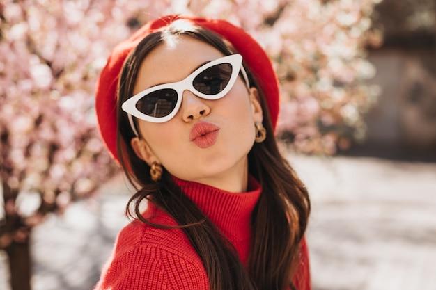 Nette dame in baskenmütze und sonnenbrille bläst kuss gegen hintergrund von sakura. attraktive stilvolle frau im roten pullover, der kokett im garten aufwirft