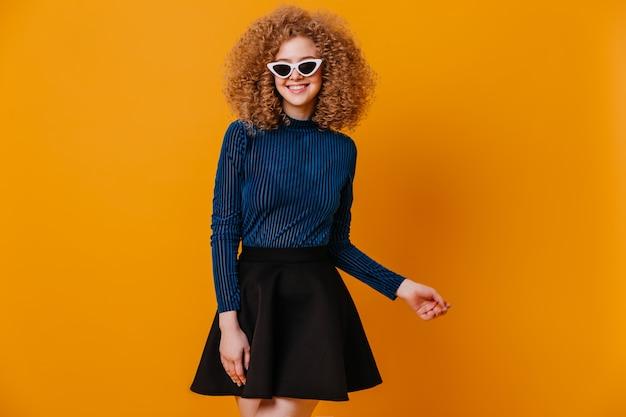 Nette dame in der sonnenbrille, die auf gelbem raum aufwirft. schuss des lockigen mädchens im blauen pullover und im schwarzen rock.