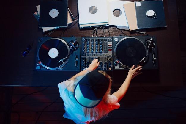 Nette dj-frau, die spaß hat, musik an der vereinpartei zu spielen