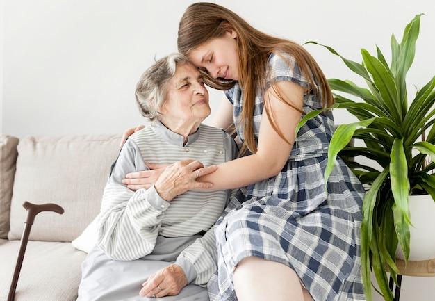 Nette enkelin, die großmutter umarmt