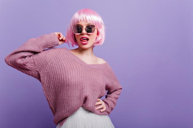 Nette europäische frau in der bunten perücke, die mit zunge heraus aufwirft. selbstbewusstes glückseliges mädchen mit rosa haaren, die brille und lila pullover tragen.