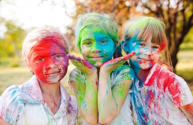 Nette europäische kindermädchen feiern indisches holi festival mit buntem farbenpuder auf gesichtern und körper