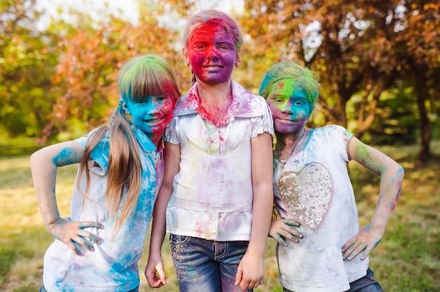 Nette europäische kindermädchen feiern indisches holi-festival mit buntem farbpulver auf gesichtern und körper