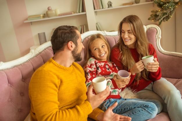 Nette familie, die auf dem sofa sitzt und sich gut fühlt