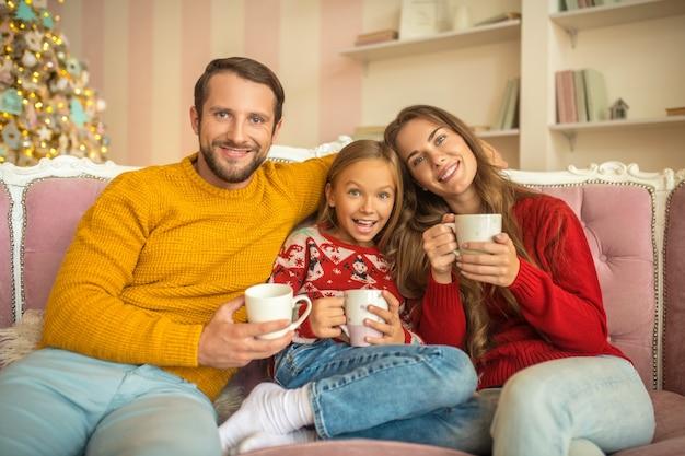 Nette familie, die auf dem sofa sitzt und sich wohl fühlt
