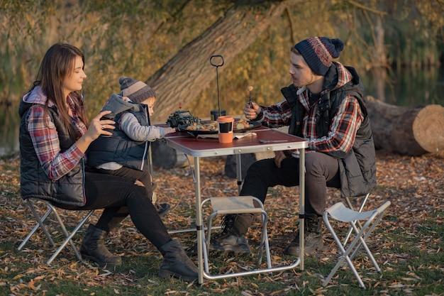 Nette familie, die auf einem picknick in einem wald sitzt