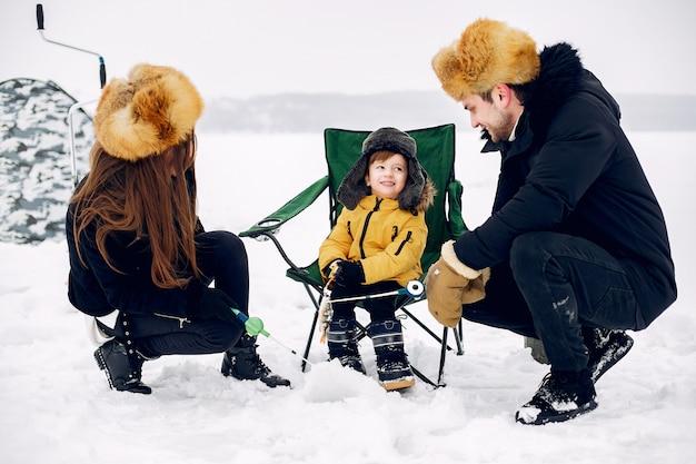 Nette familie, die auf einem winterfischen mit kleinem sohn sitzt