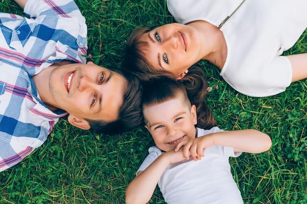 Nette familie, die auf gras in einem kreis liegt und kamera betrachtet.