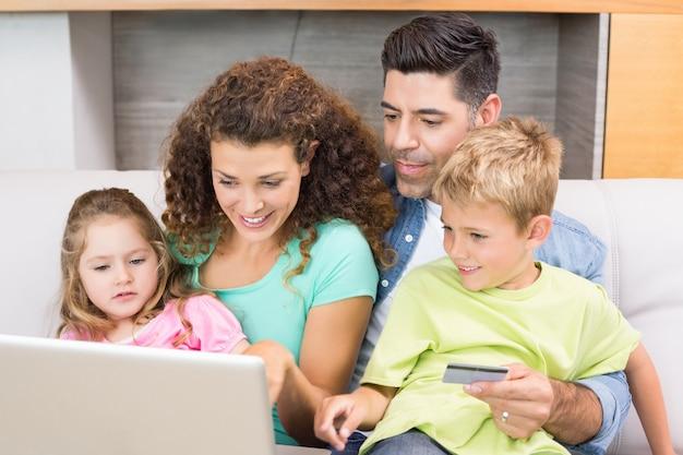 Nette familie, die auf sofa mit dem laptop online kauft sitzt