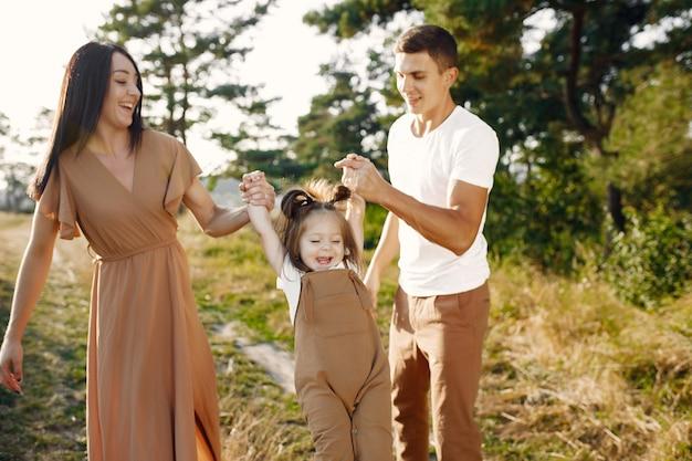 Nette familie, die in einem herbstfeld spielt