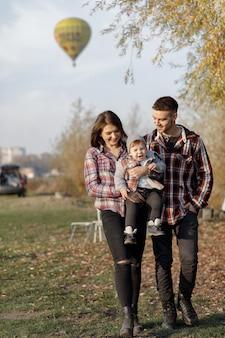 Nette familie, die in einem sonnenuntergangssommerpark geht