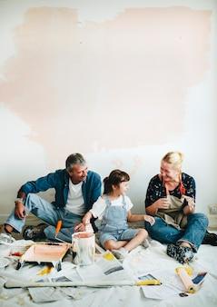 Nette familie, die nach dem malen der wände sich entspannt