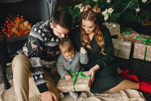 Nette familie, die nahe weihnachtsbaum sitzt