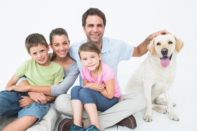 Nette familie mit haustier labrador, das zusammen an der kamera aufwirft und lächelt