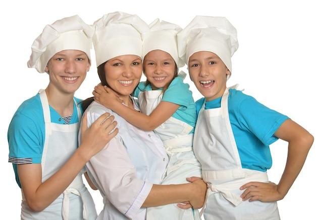 Nette familie posiert in kochuniformen mit daumen nach oben isoliert auf weißem hintergrund