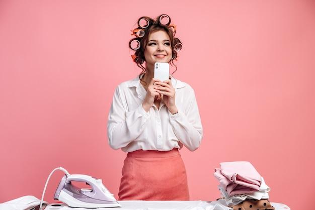 Nette, faszinierte hausfrau mit lockenwicklern, die ein telefon in ihren händen an einer rosa wand halten