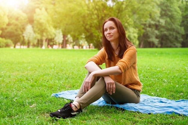 Nette frau, die auf einer matte auf dem gras im park sitzt und sich ausruht