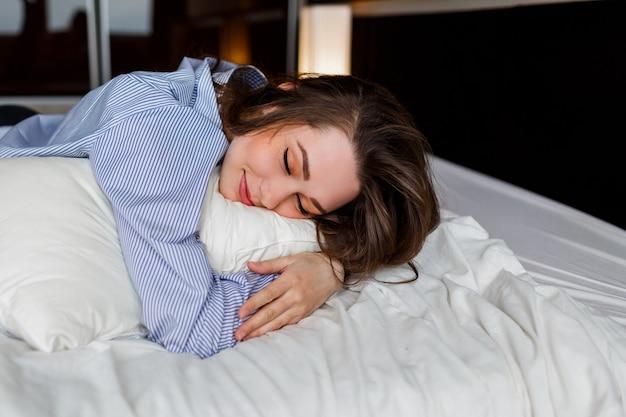 Nette frau, die auf ihrem bauch auf dem bett liegt und schläft. tragen von stilvollen schwarzen dessous und gestreiftem boyfriend-shirt.