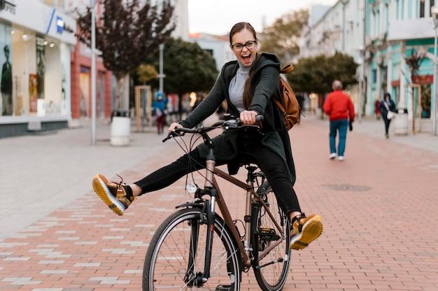 Nette frau, die auf ihrem fahrrad herumalbert