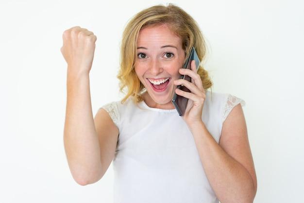 Nette frau, die auf smartphone spricht und erfolg feiert