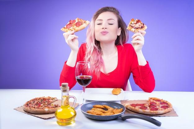 Nette frau, die den geschmack von zwei verschiedenen scheiben pizza vergleicht