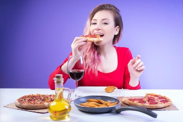 Nette frau, die ein stück pizza beißt