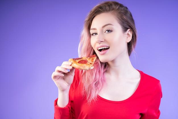 Nette frau, die ein stück pizza isst