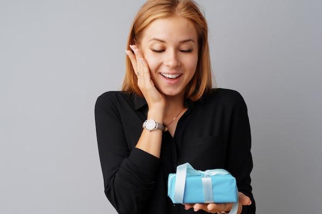 Nette frau, die eine blaue geschenkbox in ihren händen hält