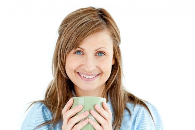 Nette frau, die einen tasse kaffee lächelt an der kamera hält