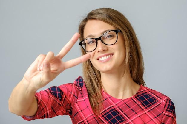 Nette frau, die friedenszeichen mit ihren fingern zeigt