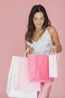 Nette frau, die rosa einkaufsnetz untersucht