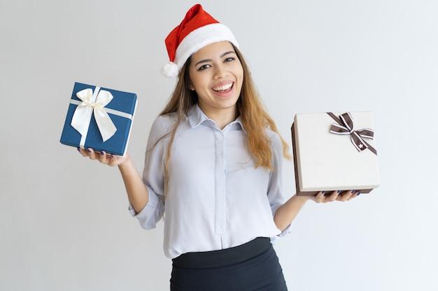 Nette frau, die santa claus-hut trägt und geschenkboxen zeigt