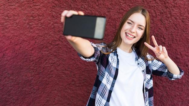 Nette frau, die selfie mit friedenszeichen auf strukturiertem hintergrund der rauen wand nimmt