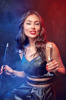 Nette frau, die shisha raucht und cocktail in einer bar trinkt