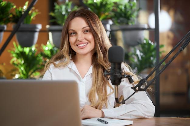 Nette frau, die sich auf interview online mit mikrofon vorbereitet