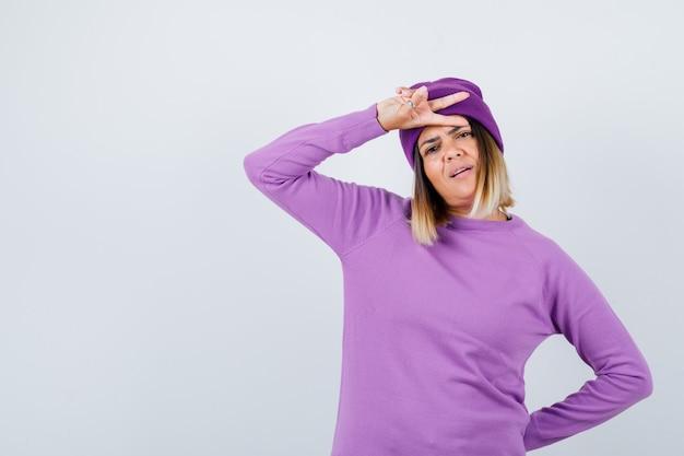 Nette frau, die siegesgeste in pullover, mütze zeigt und stolz aussieht, vorderansicht.