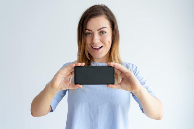 Nette frau, die smartphoneschirm zeigt