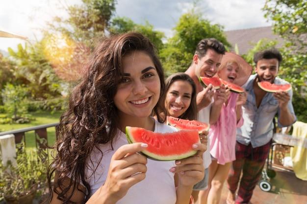 Nette frau, die wassermelonen-scheiben-lächeln zusammenhält