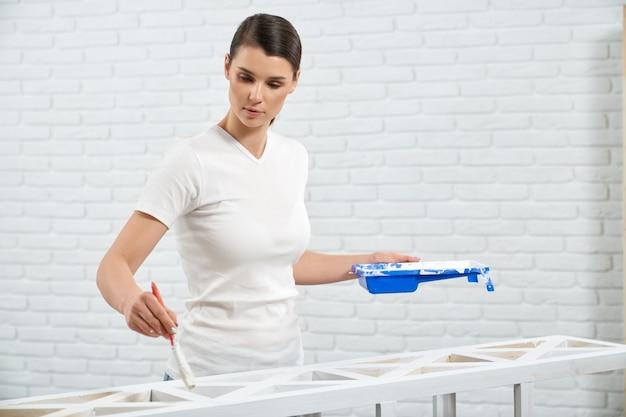 Nette frau, die weiße farbe hält und holzregal malt