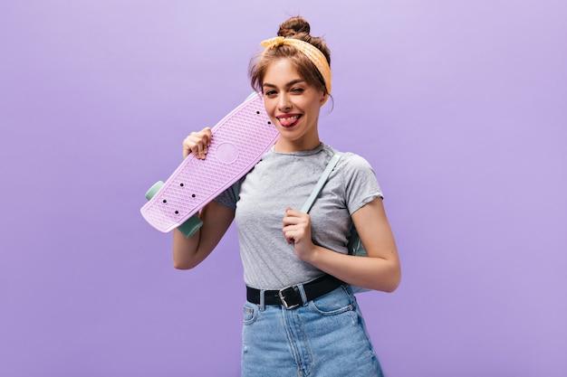 Nette frau im grauen hemd zeigt zunge, zwinkert und hält skateboard. nettes mädchen im grauen t-shirt und im jeansrock, der aufwirft.